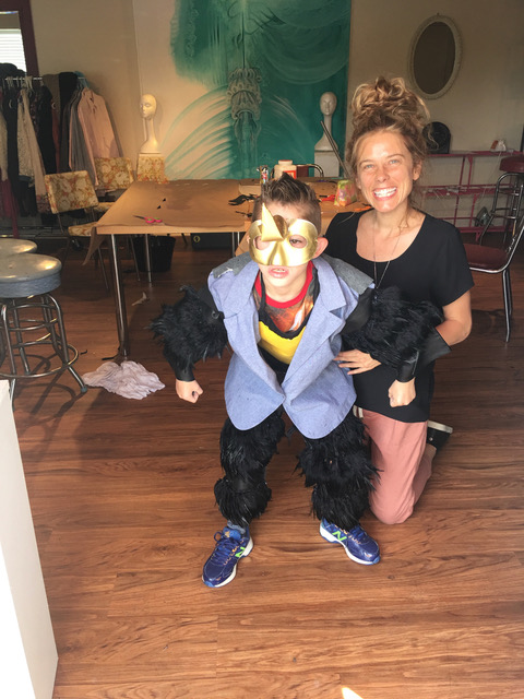 Mom smiling with son posing in gorilla outifit