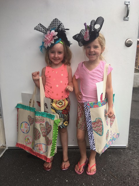 two girls holding hand created bags and wearing derby hats